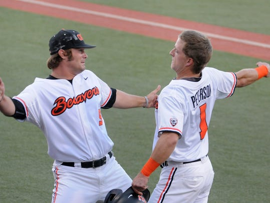 Oregon State's Ben Wetzler (9) and Andy Peterson (1) prepare to lock arms in celebration of Peterson scoring a run against UC Irvine during an NCAA college baseball regional tournament game in Corvallis, Ore., Sunday, June 1, 2014. (AP Photo/Mark Ylen)