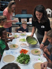 Wichita Falls Area Food Bank Nutrition Services Director Jessica Bachman spoons out avocado for veggie wraps during the Summer Education Program at the Farmers Market Tuesday. The programs run every Tuesday and Thursday through the summer with activities for children and adults.