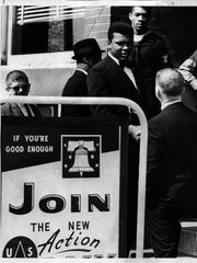 Muhammad Ali shakes hands with a man before entering Selective Service headquarters on Broadway March 17, 1966, to protest his draft reclassification .