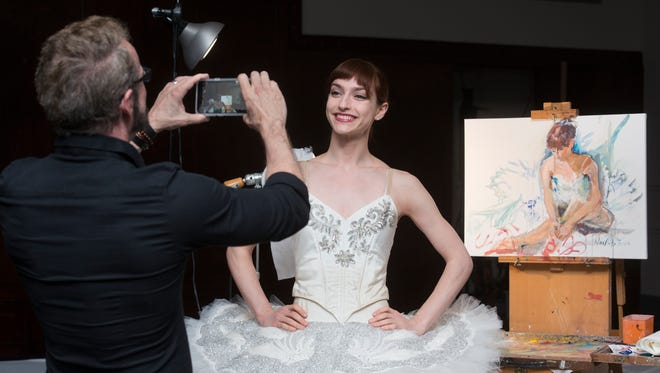 Professional dancer Scarlett Rustemeyer poses for a photo in front of the portait that was painted by artist Nina Fritz during the Live Painting Happy Hour raising money for Ballet Pensacola at the Pensacola Cultural Center on Thursday, March 29, 2018.