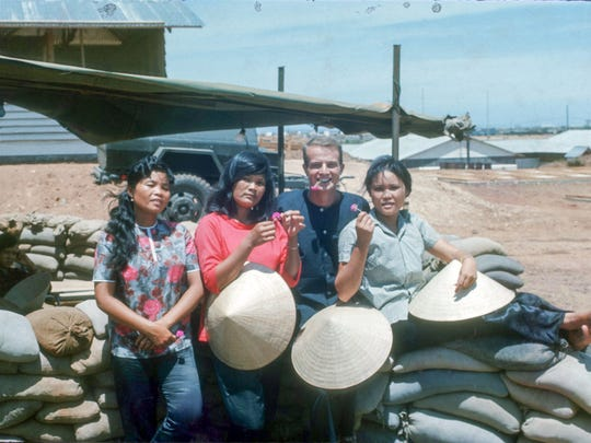 """This photo of John Whitener with three Vietnamese women appears on the back cover of his memoir, """"Don't Ask and I Will Tell."""""""