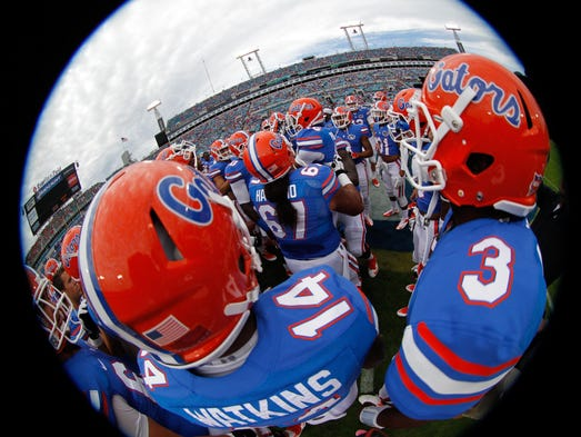 Nov 2, 2013; Jacksonville, FL, USA; Florida Gators defensive back Jaylen Watkins (14) and quarterback Tyler Murphy (3) and teammates huddle up against the Georgia Bulldogs prior to the game against the Florida Gators at EverBank Field. Mandatory Credit: Kim Klement-USA TODAY Sports