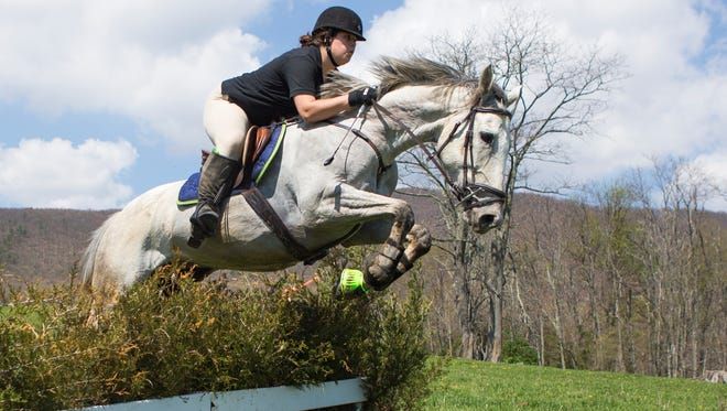 Jessie Clark, 19, leaps her horse Misty over a jump during the Glenmore Hunt Club's spring hunter pace event on Saturday, April 18, 2015. The event simulates a fox hunt taking riders through a roughly eight-mile loop crossing streams, open fields and traveling through woods.