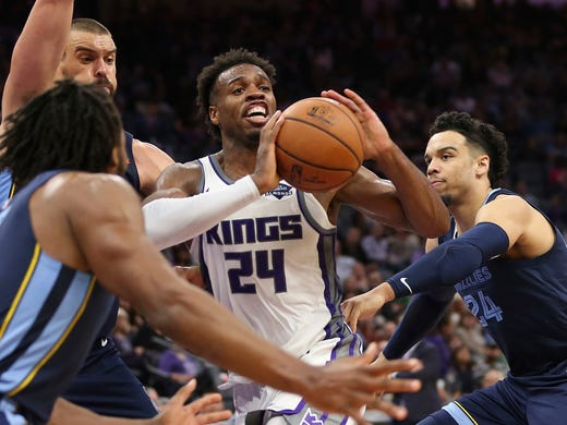 Sacramento Kings guard Buddy Hield, center, passes as he is triple-teamed by Memphis Grizzlies' Wayne Selden, left, Marc Gasol, second from left, and Dillon Brooks during the second half of an NBA basketball game, Wednesday, Oct. 24, 2018, in Sacramento, Calif. The Kings won 97-92. (AP Photo/Rich Pedroncelli)