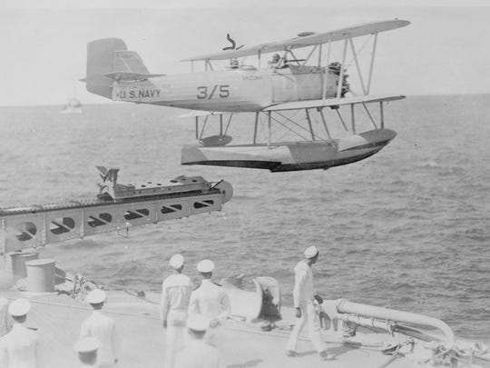 The battleship launched small planes from a catapult on deck. Later, cranes would retrieve them from the water.