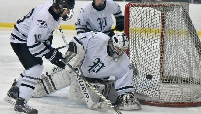 Plymouth senior goalie Brendan Olepa (1) seals off a Livonia Stevenson shot during the Division 2 pre-regional on Feb. 27. Helping Olepa are teammates Jeffrey Koviak (10) and Andrew Garby (6).