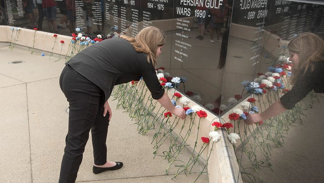 Kaylee Traster places a carnation at the memorial wall.
