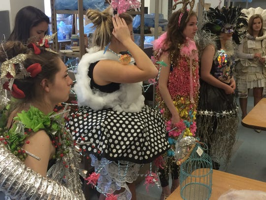 Models line up wearing student designed fashions, using