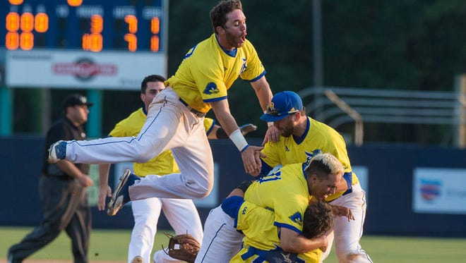 Pitcher Kyle Hinton is mobbed by teammates after Delaware won the CAA title Saturday at UNC-Wilmington in 2017.