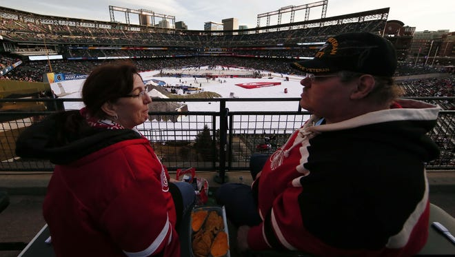 Two Red Wings fans enjoy the scene — and apparently some nachos — at Coors Field on Saturday before the Wings met the Colorado Avalanche in the NHL Stadium Series.