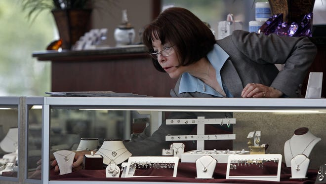 In a 2012 file photo, assistant manager Kathie Schwalbach adjusts a jewelry display in A&E Jewelers' Neenah store.