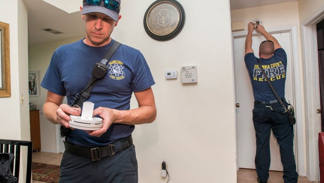 Matt VanMatre, left, installs a battery in a smoke detector as fellow Escambia County Firefighter Shaun Straut prepares to hang it at the home of Mia Woolfolk in Pensacola on Monday, July 31, 2017.