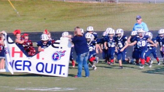 Fairview Titan PeeWee cheerleaders and football players rush the field.