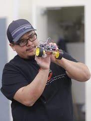 Electrical engineering student Conrad Begay adjusts