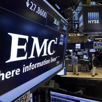 Trader Sal Suarino works near the post that handles EMC Corp. on the floor of the New York Stock Exchange on Monday. Dell is buying data storage company EMC in a deal valued at approximately $67 billion.