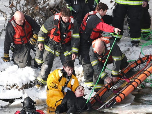 IFD Captain Casey Sweeney hands off a woman who apparently jumped off the 16th Street bridge into the White River. The woman was then taken to Eskenazi Health on Monday, January 20, 2014.
