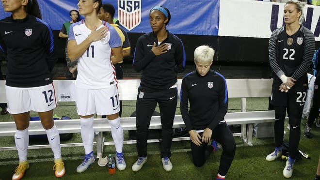 In this Sept. 18, 2016, file photo, Team USA's Megan Rapinoe, right, kneels next to teammates Christen Press (12), Ali Krieger (11), Crystal Dunn (16) and Ashlyn Harris (22) as the national anthem is played before the team's exhibition soccer match against the Netherlands in Atlanta.