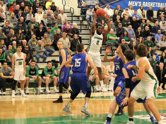 York College's Jason Bady, center, leaps as he looks to pass during Saturday's NCAA Division III men's basketball tournament second-round game against Hamilton College in York.