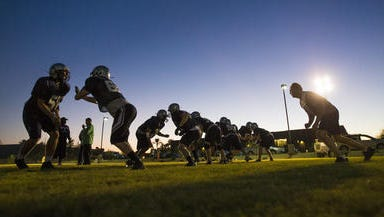 Scottsdale Prep head coach Shawn Wright (right) works with his linemen during practice in Scottsdale on Oct. 21, 2014.