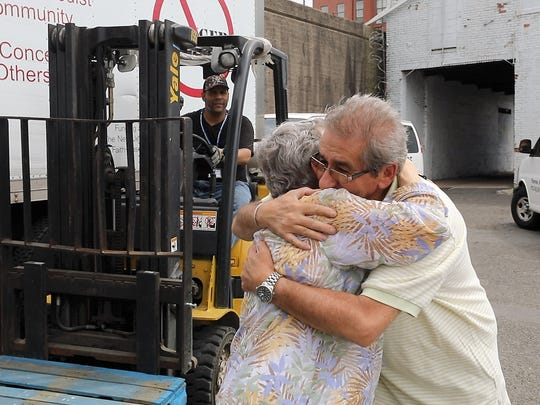 The Rev. Patricia Bruger hugs Bert Salino of North Bergen, a driver with CUMAC for the past five years.