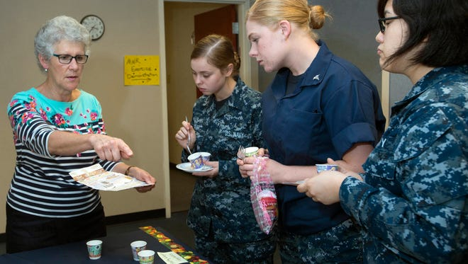 Dietician Shelley Pino, left, gives sailors, Victoria Piper, center, Dayna Horn, right center, andSou-Chree Lor, right, tips on balanced diets and nutrition during a wellness fair at the Pensacola Naval Hospital. The Naval Hospital has started a new Integrated Health Communities Program.