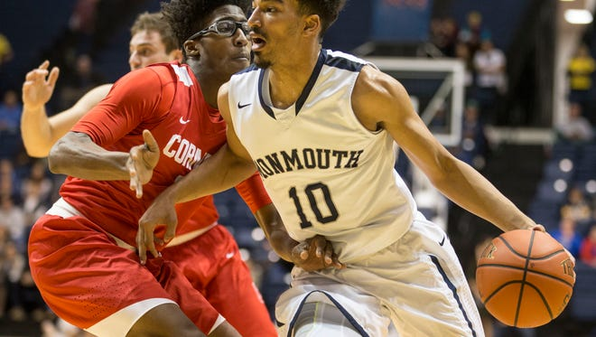 Monmouth's Micah Seaborn drives past Cornell's Robert Hatter. Monmouth vs Cornell mens basketball.