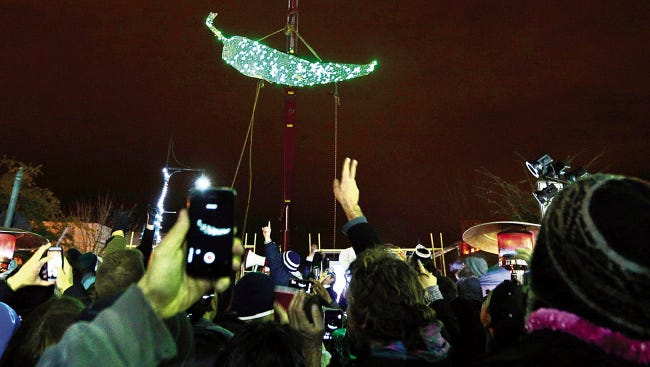 Caption: Photo: A 15-foot lighted green chile is lowered during the 2014 Chile Drop on New Year's Eve in downtown Las Cruces.