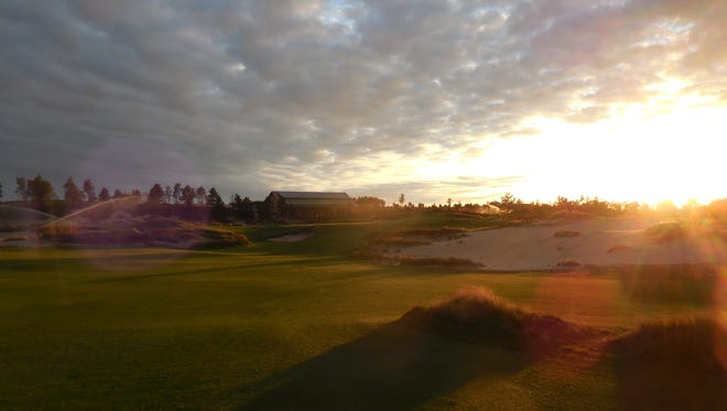 The 18th hole at Mammoth Dunes at sunset, with the clubhouse in the background.