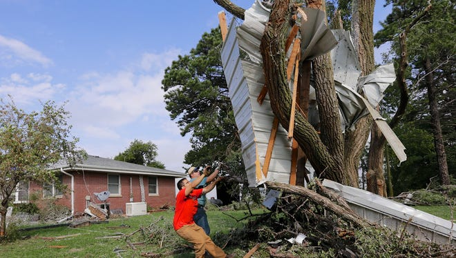Residents try to free a house panel from where it was lodged against a tree after a tornado in Bennet, Neb., on Oct. 4, 2013.