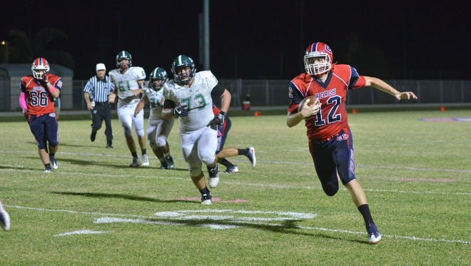 Cocoa Beach quarterback Mitchell Machock runs in the final touchdown of the first half against Father Lopez High School.