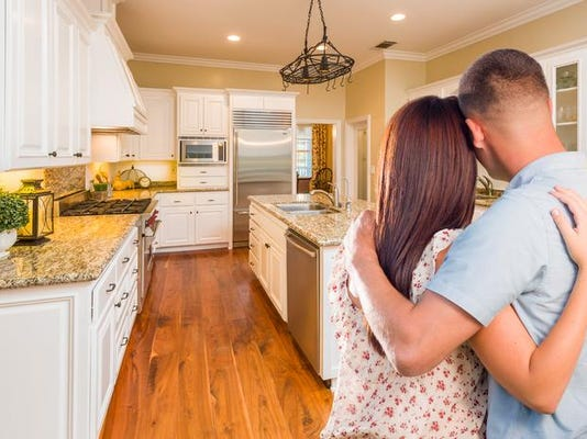 Young Hopeful Military Couple Looking At Custom Kitchen