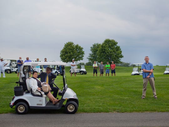 Golf club players join members of the White House staff and security on the course as they all stop to listen to President Donald Trump speak at Trump National Golf Club in Bedminster, N.J., Friday, Aug. 11, 2017.