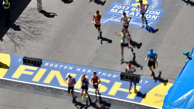 Runners cross the finish line at the 2017 Boston Marathon.
