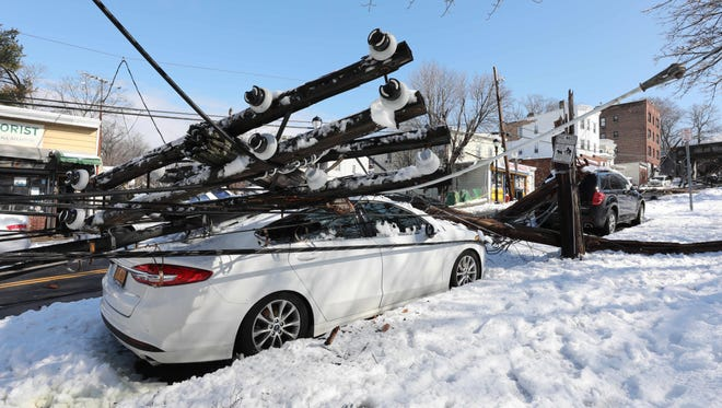 Utility poles fall across a car in Yonkers, N.Y., during the nor'easter March 8, 2018.