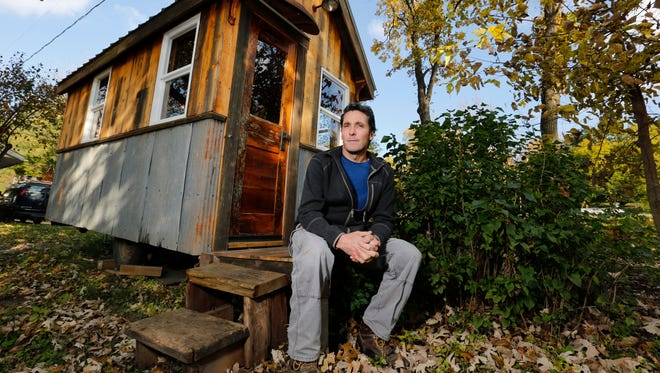 Sean Spain of Johnston, Iowa, builds 100-square-foot tiny homes. They are built largely with reclaimed materials. At 14 feet by 7 feet, it includes a kitchenette, loft, restroom, custom cabinetry and a fold-down deck, all built on a trailer.