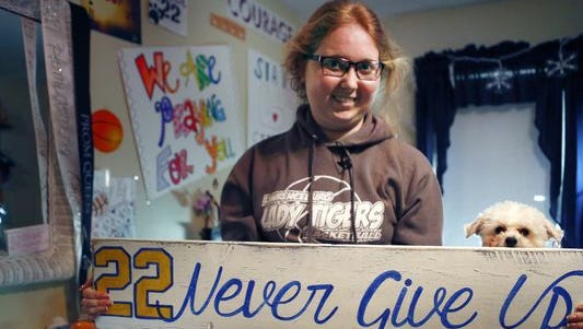 Lauren Hill holds a sign made for her, which she keeps in her room, along with many other messages and gifts of support. Her dog, Sophie, is at her side.
