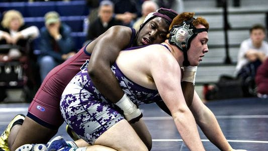 Eastern's Izzy Brooks (left) wrestles Cherry Hill West's Eric Barnett in the heavyweight class on Saturday at Eastern. Brooks won the match and so did his team. The Vikings beat the Lions 50-17.