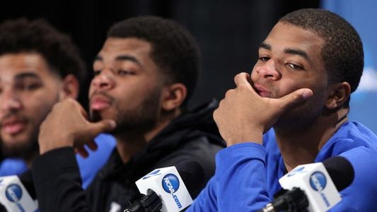 Aaron Harrison of the Kentucky Wildcats reacts in the post game press conference with Andrew Harrison and Willie Cauley-Stein after being defeated by the Wisconsin Badgers during the NCAA Men's Final Four Semifinal at Lucas Oil Stadium on April 4.