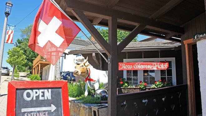 """Swiss flags and painted cow sculptures add to the charm of New Glarus, dubbed """"America's Little Switzerland."""""""