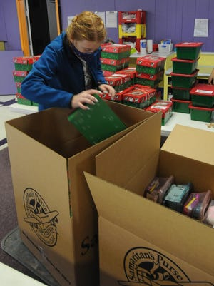 Mia Smith, 14, loads the Operation Christmas Child boxes into a bigger box that will be sent to children in need around the world during the collection week at the drop-off lo-cation at the CrossRoads Church, 1125 W. South Street, in Salina on Friday afternoon. The location has collected over 1,200 boxes as of Friday. Operation Christmas Child boxes contain essential items such as soap, wash cloth, toothbrush, along with toys.