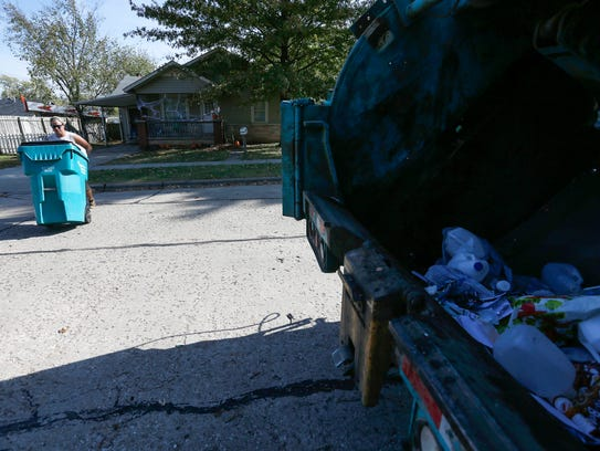 Thomas Nault, of Queen City Disposal, picks up trash