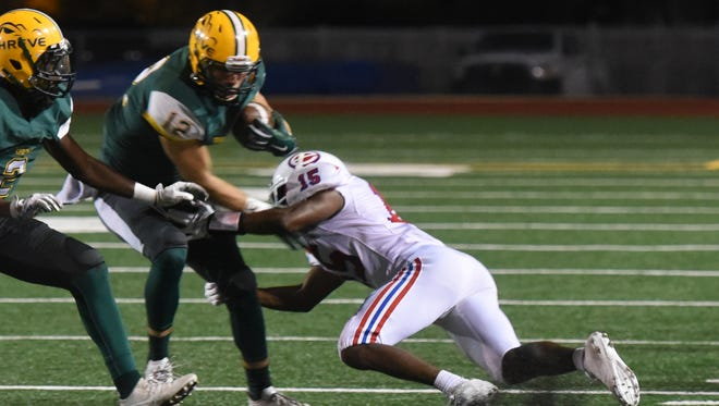 Captain Shreve receiver Stephen Smith tries to get free of an Evangel defender Thursday evening at Lee Hedges Stadium.