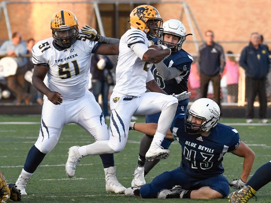Battle Creek RB Antonio Postell (2) prepares to leap over a Gull Lake defender early in Friday night's matchup at Gull Lake.