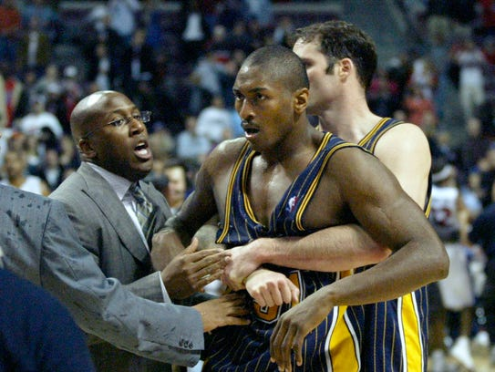 Ron Artest is restrained by Austin Croshere before