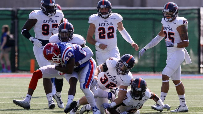 Louisiana Tech running back Kenneth Dixon tries to escape an UTSA tackler during last year's 27-20 win.l