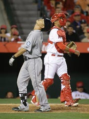 Seattle Mariners' Norichika Aoki, left, of Japan, reacts after striking out, as Los Angeles Angels catcher Carlos Perez throws the ball to relief pitcher Fernando Salas during the seventh inning of a baseball game, Friday, April 22, 2016, in Anaheim, Calif. (AP Photo/Jae C. Hong)