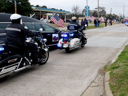 People watch and hold American flags for Shreveport Police Department officer ChatŽri Payne's procession down Jewella Ave.