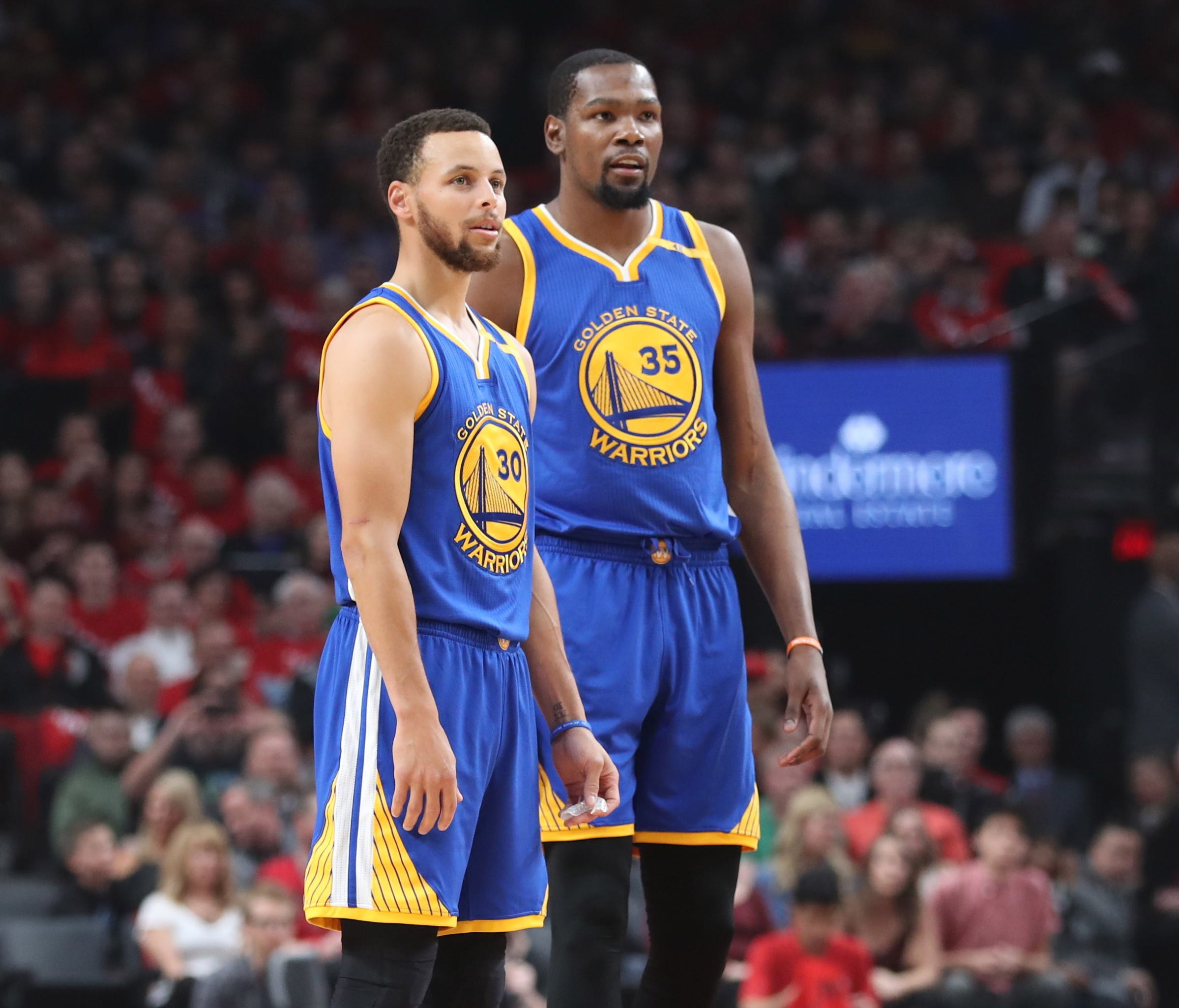 Stephen Curry and Kevin Durant look on from the court in the first half of Game 4 of the first round of the 2017 NBA Playoffs.