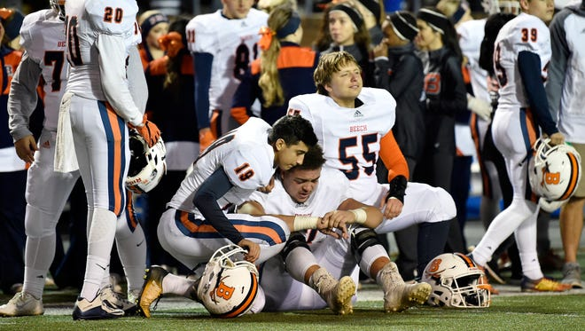 Beech's Alex Anki (19), Cole Pulley (67) and Zach Stahl (55) console each other after the team's 45-28 loss to Knoxville Catholic in the Class 5A state championship game at Tucker Stadium in Cookeville, Tenn., Thursday, Nov. 30, 2017.