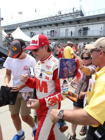 Jeff Gordon is swarmed by fans and media as he walks